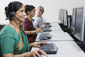 Female Customer Service Operator Working With Colleagues At Office — Stock Photo