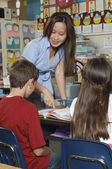 Teacher Helping Students In Classroom — Stockfoto