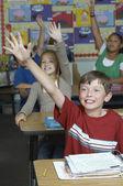 öğrenciler sınıfta eller yükselterek — Stok fotoğraf