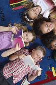 Students Reading Books While Lying On Carpet — Foto Stock