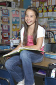 Girl Sitting On Desk With Book — Stock Photo
