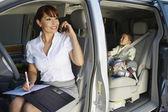 Femme d'affaires à l'aide de téléphone portable avec fils en voiture — Photo