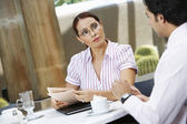 Businesswoman Holding Newspaper While Looking At Colleague — Stock Photo