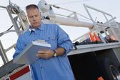 Mechanic Writing Notes On Clipboard Against A Truck — Stock Photo
