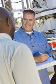 Mechanic Looking At Client While Writing On Clipboard — Stock Photo