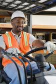 Mâle ouvrier industriel, conduite de chariot élévateur sur lieu de travail — Photo