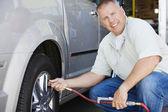 Mechanic Inflating RVs Tire — Stock Photo