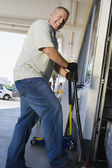Man Jacking Up Vehicle In Service Station — Stock Photo