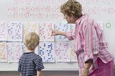 Lehrer kalender, kleinen jungen zu erklären — Stockfoto