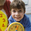 Boy Showing Yellow Clock With Teacher In Background — Foto de Stock
