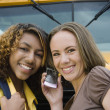 Friends Using Cell Phone By School Bus — Stock Photo