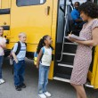 Children Standing In A Line By School Bus — Stock Photo #21831985