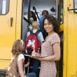 Teacher Loading Elementary Students On School Bus - Stockfoto
