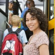 Teacher Loading Elementary Students On School Bus - Stock Photo