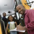Teacher Unloading Elementary Students From School Bus — Stock Photo #21832283