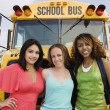 Teenage Girls By School Bus - Stock Photo