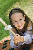 Dressed Up Little Girl Climbing A Rope — Стоковое фото