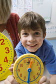 Boy Showing Yellow Clock With Teacher In Background — Stock Photo