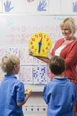 Teacher Teaching Kids To Tell Time — Stock Photo