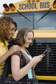 Students Text Messaging By School Bus — Stock Photo