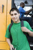 High School Boy With MP3 Player Getting Off School Bus — Stock Photo