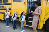 Children Standing In A Line By School Bus — Stok fotoğraf