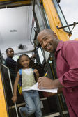 Teacher Unloading Elementary Students From School Bus — Stock Photo