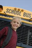 Niño parado delante de autobús escolar — Foto de Stock