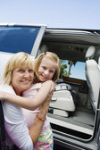 Grandmother Hugging Granddaughter By Minivan — ストック写真