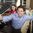 Stock Photo: Man Holding Car Key With Woman Beside Him In Convertible