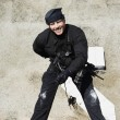 Foto Stock: SWAT Team Officer Rappelling from Building