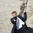 Foto Stock: Male Spy Aiming Handgun While Rappelling