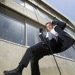 Stock Photo: Spy Rappelling And Using Cell Phone