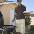 Man Barbequing In Lawn - Stock Photo