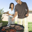 Happy Couple Barbequing - Stock Photo