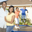 Happy Couple With Children Playing On Trampoline — Stock Photo