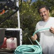 Man Holding Hose In Garden — Stock Photo