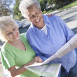 Two Happy Senior Women Reading Map — Foto Stock