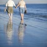 Senior Couple Walking Together On Beach — Stock Photo #21866657