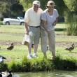 Happy Senior Couple Feeding Ducks — Stock Photo #21869803