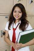 Wysoki uczennice gospodarstwa podręcznik przez szkolną — Zdjęcie stockowe