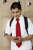 High School Boy Text Messaging By School Lockers — Stock Photo