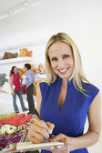 Beautiful Saleswoman With Customers In Background — Stockfoto