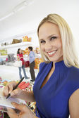 Woman Signing A Receipt In Home Furnishings Store — Stock Photo