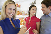 Saleswoman And Couple At Store — Stockfoto
