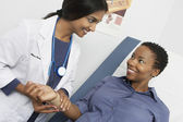 Female Doctor Checking Patient's Pulse — Stock Photo