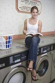 Frau sitzt auf Waschmaschine im Waschsalon — Stockfoto