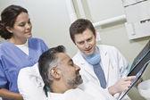 Tandläkare förklara röntgen rapporterar till patienten — Stockfoto