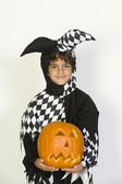 Boy In Jester Outfit Holding Jack-O-Lantern — Stock Photo