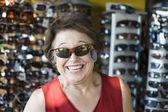 Starszy kobieta próbuje okulary w sklepie — Zdjęcie stockowe